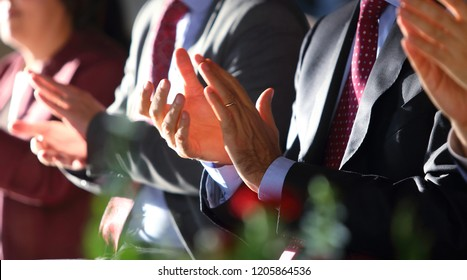 The people in suit are clap the hands with the rim light and blur background.