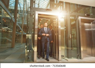 people in suits come out of Elevator and walk around the office