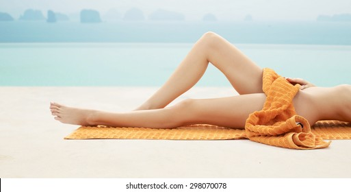 people, summer, beauty and vacation concept - close up of woman legs with orange towel at resort beach or pool