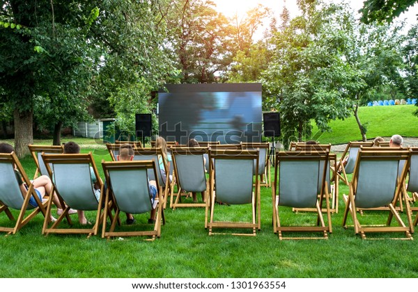 People in a summer cinema are watching a movie.