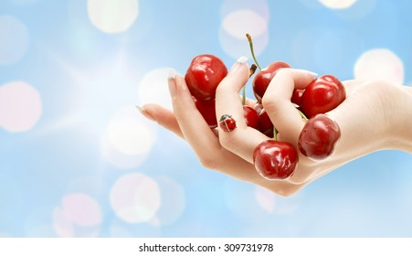 people, summer, fruits hand berries concept - female hand full of red cherries over blue lights background