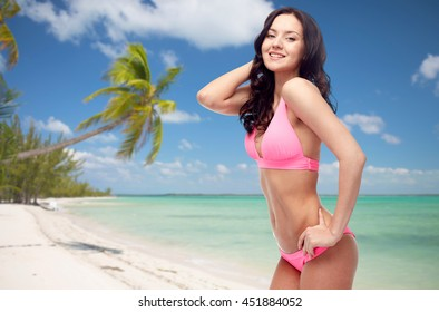people, summer holidays, travel and tourism concept - happy young woman posing in pink bikini swimsuit over exotic tropical beach with palm trees background,