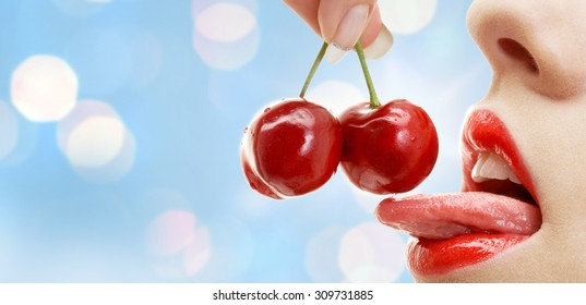 people, summer, sexual and erotic concept - woman mouth with lips and tongue eating ripe red cherry over blue lights background