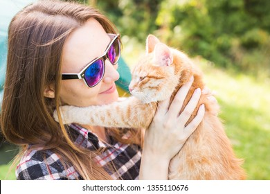 people, summer tourism and nature concept - young woman with cat near tent
