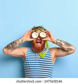 People, summer vacation, snorkeling and swimming concept. Funny bearded ginger man wears snorkel mask, striped sailor t shirt, keeps two coconuts on eyes, looks into distance, has fun at beach