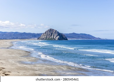 People sunbathing near Majestic Morro Rock over looking the Pacific Ocean, next to Morro Strand state beach, on the California Central Coast, near Cambria, CA.