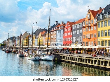 People  at sunny Nyhavn embankment with moored yachts, Copenhagen, Denmark