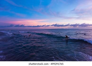 People surfing during sunset at Batu Bolong Beach in Canggu, Bali, Indonesia