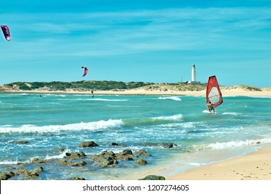 People surfing in front of the lighthouse of Trafalgar, on the beach of Los Caños de Meca, south of Spain