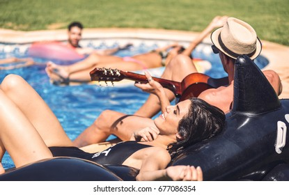People swimming with inflatable toys while man sitting and playing guitar on poolside.