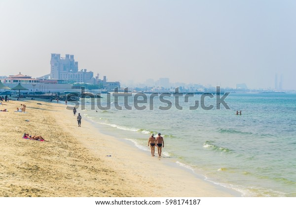 People are swimming on a beach in Ajman and look at Dubai in background.