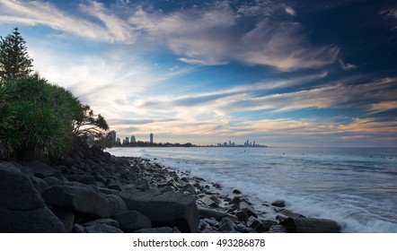 People Swimming at a Rocky Beach With a Pandanus Tree and Overlooking the Cityscape of the Gold Coast During a Calm Sunset, Burleigh Heads, Queensland, Australia