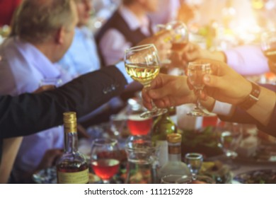 People at the table raise a toast. Close-up glasses
