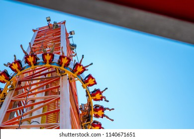People take off to a high tower in the amusement Park in the summer.