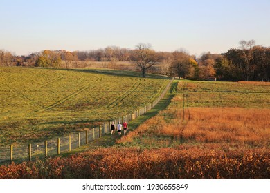 People taking a leisure walk on the trail at Stroud Preserve before sunset in late fall, West Chester, Pennsylvania, USA