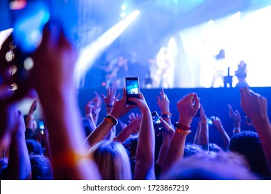 People taking photographs with smart phone during a music festival. Fans enjoying rock concert with light show and clapping hands.