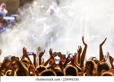 People taking photographs with touch smart phone during a music entertainment public concert