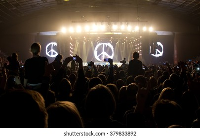 People taking photographs with touch smart phone during a music concert live on stage