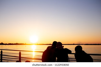 People taking photos at the sunset in Porto Alegre, southern Brazil. Taken in june 2018 in the new boat dock of Gasometro