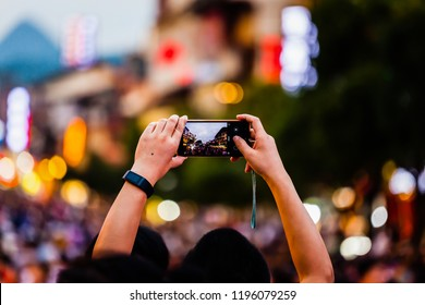 People taking photos with their mobile phone of crowds walking down west street Yangshuo county Guilin China 6th and 7th of August 2018