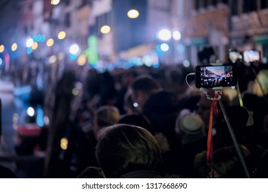 People taking pictures with a smarphone and selfie stick during the opening of the Venice Carnival 2019. Venice, Italy. February 16, 2019.