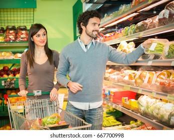 People taking vegetables in a supermarket