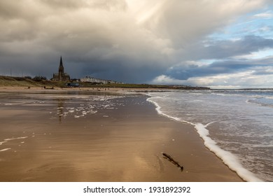 People taking a walk on Tynemouth's Longsands beach during Lockdown on a cloudy and rainy day, in the north east of England
