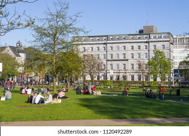 People talking and resting in Eyre Square Park, Galway, Ireland