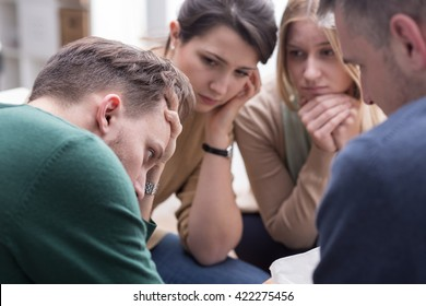 People talking together and comforting young man during group therapy session
