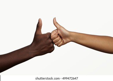 People, teamwork, cooperation, communication and partnership concept. African friends or partners showing thumbs up, holding hands close to each other as symbol of success on white wall background