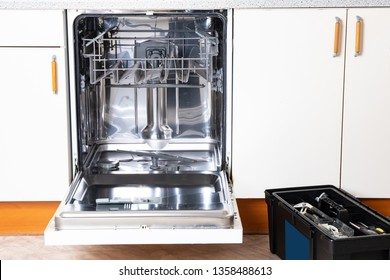 People in technician jobs. A broken built-in dishwasher with open door in a white kitchen and the service technicians toolbox.