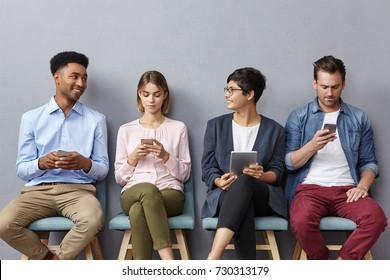 People, technology and communication concept. Four interracial people meet accidentaly in office bilduing, wait for meeting with boss, use electronic devices, enjoy pleasant lively conversation