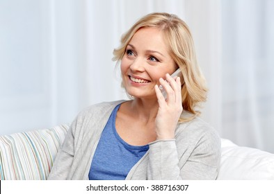 people, technology and communication concept - smiling woman calling on smartphone at home