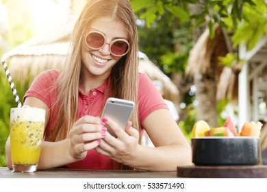People, technology and communication. Cute girl with cell phone surfing Internet, checking newsfeed via social networks, using free wi-fi, sitting at table with fruit shake. Selective focus on face