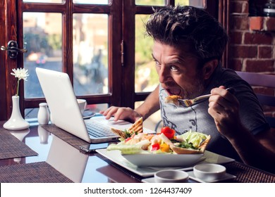 People, technology, communication and leisure concept. Hungry man sitting in cafe surfing internet, checking newsfeed via social networks, messaging friends online during lunch