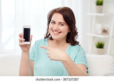 people, technology, communication and leisure concept - happy young plus size woman sitting on sofa and showing smartphone blank screen at home