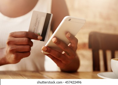 People and technology concept. Cropped portrait of young woman wearing white top holding credit card, transferring money from her account via online banking application using mobile phone. Film effect