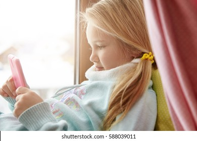 People and technology concept. Indoor shot of cute adorable Caucasian little girl lying on windowsill at home and using wi-fi on her mobile phone, watching cartoons online during winter vacations