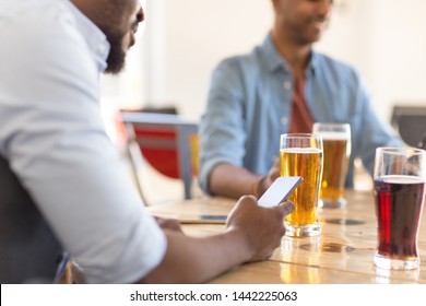 people and technology concept - man with smartphone drinking beer and reading message at bar or pub