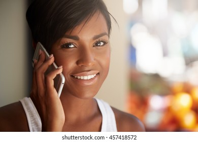 People and technology concept. Portrait of dark-skinned woman with brown eyes and short pixie hairstyle looking and smiling at the camera, showing her ultra-white teeth while making phone calls