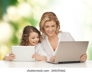 people, technology, family and parenthood concept - happy mother and daughter with laptop and tablet pc computers sitting at table over green background