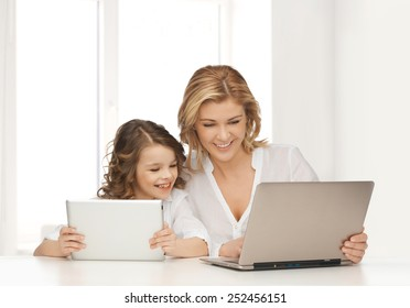 people, technology, family and parenthood concept - happy mother and daughter with laptop and tablet pc computers sitting at table over white room background