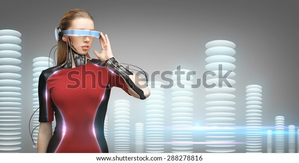 people, technology, future and progress - young woman with futuristic glasses and microchip implant or sensors over gray background with bit coin towers