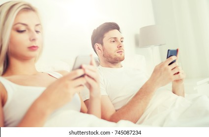 people, technology, internet and communication concept - couple with smartphones in bed