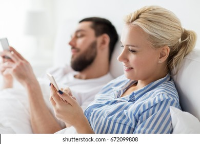 people, technology, internet, relations and communication concept - couple with smartphones in bed at home