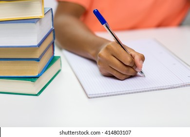 people, technology, learning and education concept - close up of african american young woman hand writing to notebook with books at home