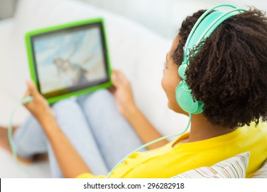 people, technology and leisure concept - close up of happy african american young woman lying with tablet pc computer and headphones listening to music and watching video at home