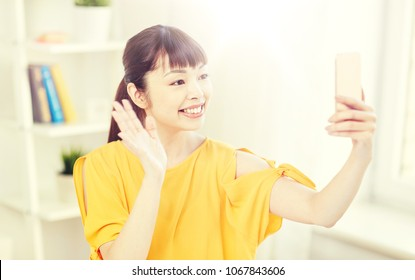 people, technology and leisure concept - happy young asian woman taking selfie on smartphone at home and waving hand