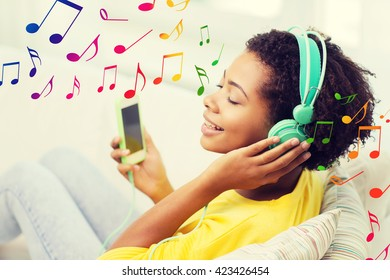 people, technology and leisure concept - happy african american young woman sitting on sofa with smartphone and headphones listening to music at home over notes background