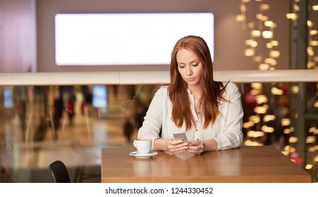 people, technology and leisure concept - woman drinking coffee and messaging on smartphone at restaurant or cafe